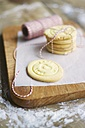Stack of home made almond cookies on a cutting board - HAWF000181