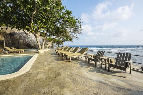 Indonesia, Riau Islands, Bintan, Nikoi Island, Sun loungers at hotel pool - THA000349