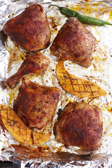 Roasted chicken, slices of sweet potato and green chili pepper on aluminium foil - KSWF001283
