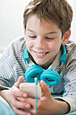 Portrait of smiling boy with smartphone and headphones lying on beanbag - LVF001286