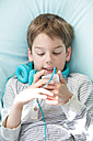Portrait of boy with smartphone and headphones lying on beanbag - LVF001287