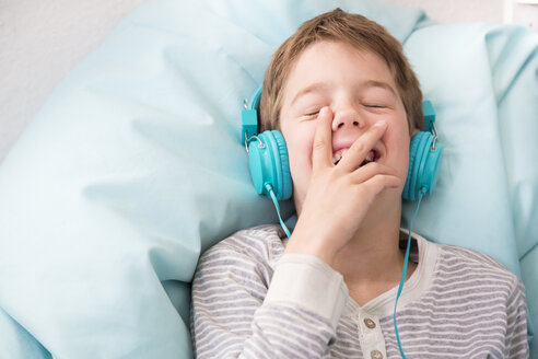 Portrait of laughing boy hearing music with headphones lying on beanbag - LVF001290