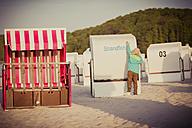 Germany, Mecklenburg-Western Pomerania, Ruegen, Boy on beach with beach chairs - MJF001182