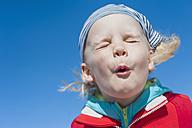 Germany, Mecklenburg-Western Pomerania, Ruegen, Boy pulling faces under blue sky - MJF001218