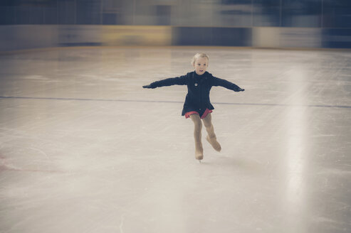 Young female figure skater moving on ice rink at competition - MJF001273