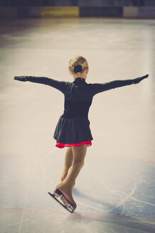 Young female figure skater moving on ice rink at competition - MJF001276
