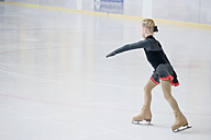 Young female figure skater moving on ice rink at competition - MJF001279