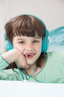 Portrait of Laughing little girl with headphones and smartphone - LVF001309