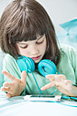 Portrait of little girl with headphones using smartphone - LVF001313