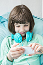 Portrait of little girl with headphones using smartphone - LVF001315