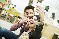 Portrait of teenage couple with popcorn photographing themself at fun fair - UUF000658