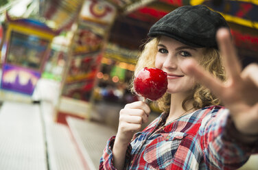 Portrait of happy teenage girl with candied apple showing victory-sign - UUF000643