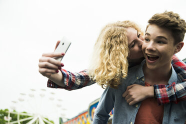 Portrait of teenage couple photographing themself at fun fair - UUF000672