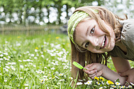 Portrait of laughing girl crouching on  flower meadow with magnifying glass - STB000170