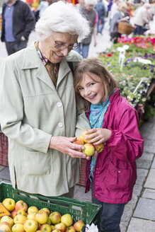 Great-grandmother and great-granddaughter choosing apples on weekly market - STB000172