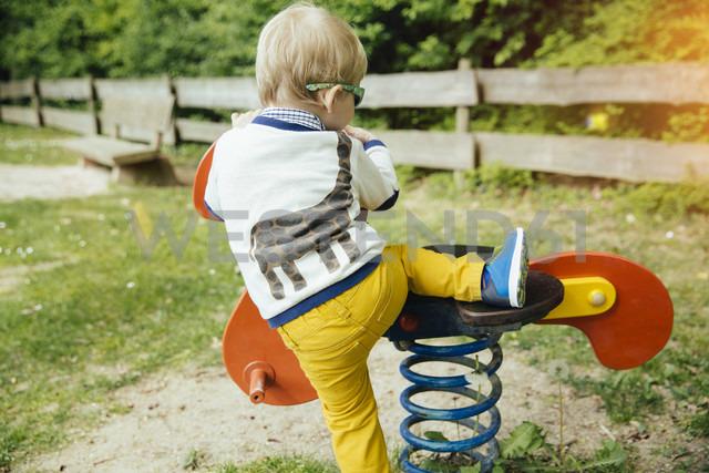 Toddler climbing on rocking animal on  playground - MFF001113