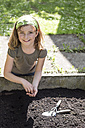 Portrait of girl sowing seeds in raised bed - STB000178