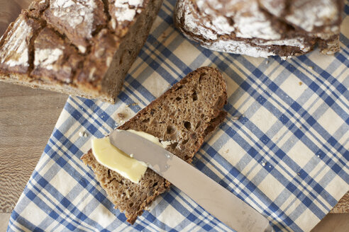 Buttering slice of wholemeal bread, elevated view - SABF000007