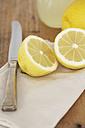 Sliced lemon, knife, cloth and glass of lemon juice on wood - SABF000029