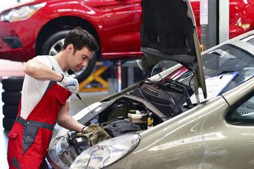 Car mechanic in a workshop working at car - LYF000019