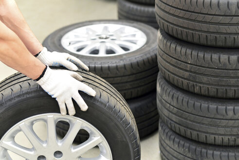 Close-up of car mechanic with tires - LYF000012