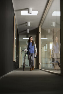Business woman arriving at office with racing cycle - FKF000565