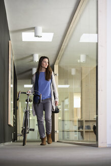 Business woman arriving at office with racing cycle - FKF000498