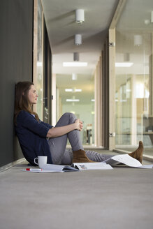 Portrait of business woman sitting on ground in corridor of office - FKF000503