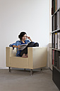 Portrait of business woman sitting on armchair reading magazine - FKF000505