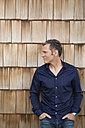 Portrait of creative business man in front of wood shingle panelling - FKF000510