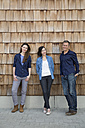 Group picture of three creative business people in front of wood shingle panelling - FKF000518
