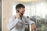 Portrait of business man telephoning with smartphone - FKF000536
