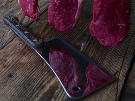 Pieces of raw beef lying on kitchen cleaver and wooden table - SRSF000496