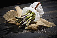 Bunch of green asparagus in white paper bag on jute and dark wood - MAEF008352