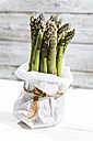 Bunch of green asparagus standing in white paper bag in front of white wood - MAEF008337