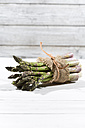 Bunch of green asparagus in front of white wood - MAEF008341