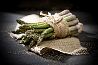 Bunch of green asparagus on jute and dark wood - MAEF008344