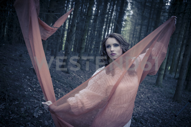 Portrait of a young woman standing in forest with outstretched arms holding cloth - VTF000255 - Val Thoermer/Westend61