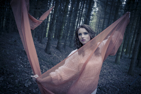 Portrait of a young woman standing in forest with outstretched arms holding cloth - VTF000255