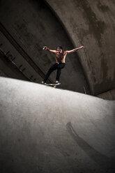 Skateboarder performing trick at skateboard park - KJ000297