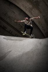 Skateboarder performing trick at skateboard park - KJ000301