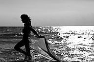 Silhouette of young woman walking at the sea - AJF000047