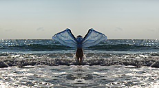 Silhouette of young woman in front of the sea holding blue cloth with outstretched arms - AJF000049