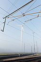 Germany, Hamburg, wind turbine next to railway track in early morning fog - MSF003980