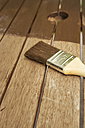 Applying glaze with brush on wooden bench, partial view - ONF000553