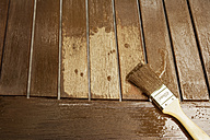 Applying glaze with brush on wooden bench, partial view - ONF000555