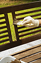 Man applying glaze on wooden bench, partial view - ONF000560