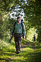 Germany, Rhineland-Palatinate, Moselsteig, young man hiking with backpack and hiking poles - PAF000703