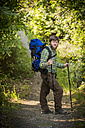 Germany, Rhineland-Palatinate, Moselsteig, young man hiking with backpack and hiking poles - PA000709