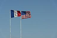 France, Normandie, Manche, Sainte Marie du Mont, Utah Beach, French and US flag waving against blue sky - JBF000111